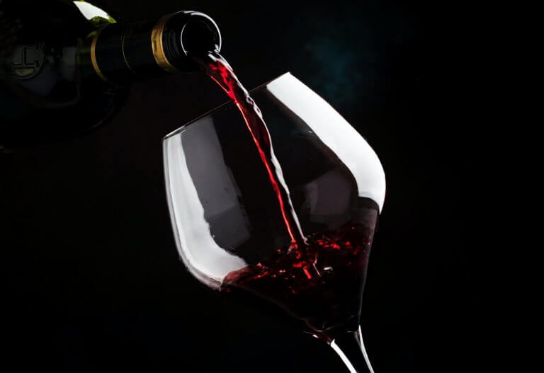 Red wine from grapes of pinot noir varieties poured into large wine glass, wine tasting